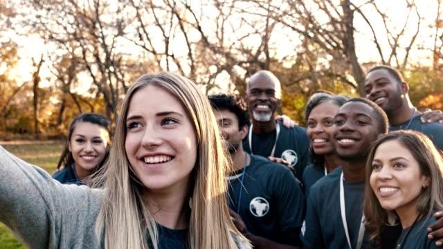 happy group of volunteers take selfie after community cleanup day - volunteer stock videos & royalty-free footage