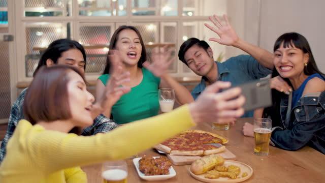スマートフォン、新しい通常のライフスタイルと社会的な離散コンセプトを介して自宅で友人とディナーパーティーやビデオ通話挨拶を楽しむ若いアジアの人々のハッピーグループ - ディナーパーティー点の映像素材/bロール
