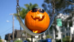 Happy Halloween pumpkin on the swing in 4K Slow motion 60fps