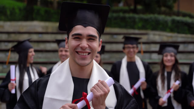 happy handsome male student celebrating he got his degree wearing a gown and cap - graduation stock videos & royalty-free footage