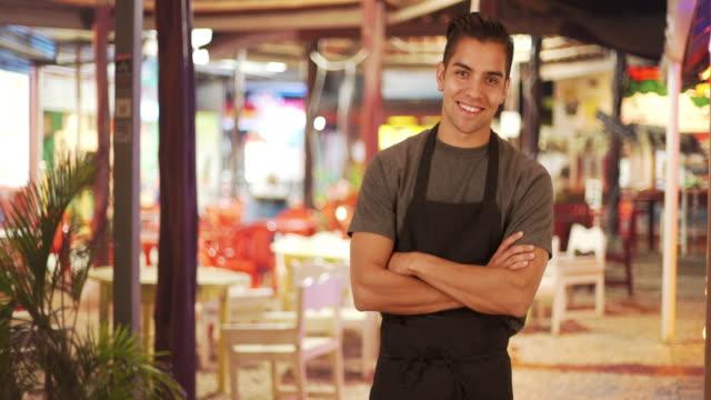 vidéos et rushes de happy handsome young latino waiter standing in outdoor patio of restaurant smiling - éléments de décoration intérieure