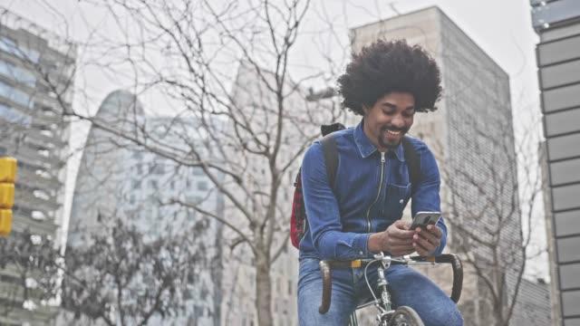 Happy hipster het controleren van een SMS-bericht zittend op de fiets