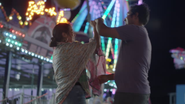 vídeos de stock e filmes b-roll de happy hispanic couple dance in front of a ferris wheel at a carnival - turning