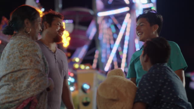 happy hispanic family chat in front of a ferris wheel at a summer carnival - wilmington north carolina stock-videos und b-roll-filmmaterial