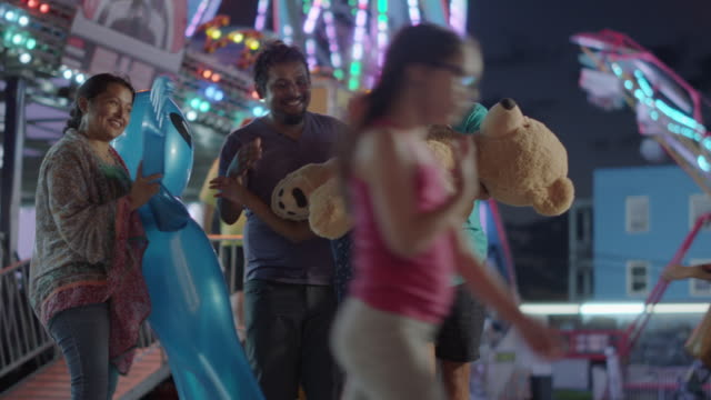 happy hispanic family chat on the midway at a summer carnival - wilmington north carolina stock-videos und b-roll-filmmaterial