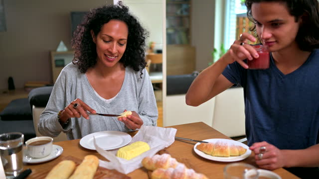 happy hispanic mother and son eating french breakfast together at home - adult stock videos & royalty-free footage