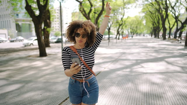 happy hispanic woman listening to music and dancing on the street - potere femminile video stock e b–roll