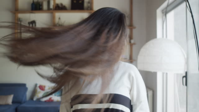 happy hispanic young adult woman tossing her hair at home - hair toss stock videos & royalty-free footage
