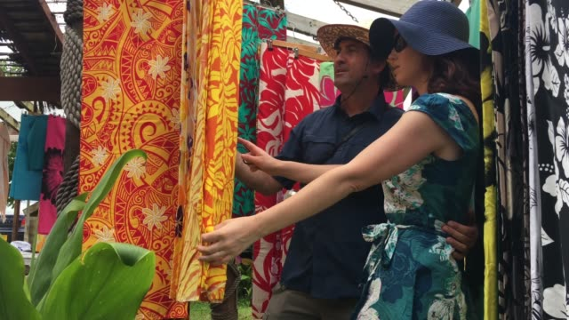 happy honeymoon looking at sarongs for sale at open market markets in a pacific island market - rarotonga stock videos & royalty-free footage