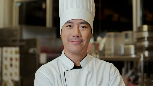 happy hotel executive chef smiling at camera with arms crossed, standing in the kitchen. - standing stock videos & royalty-free footage