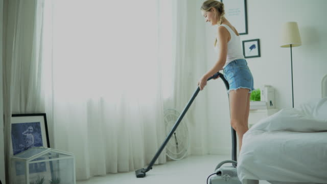 happy housewife cleaning the room with vacuum cleaner - stereotypical homemaker stock videos & royalty-free footage
