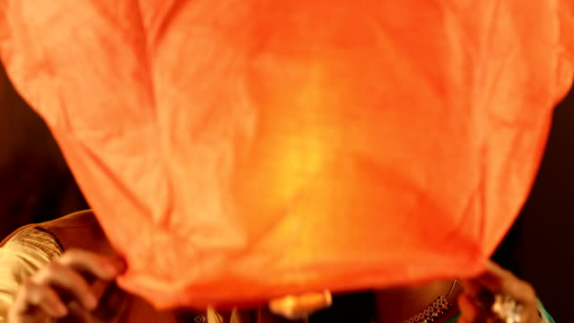 cu happy husband and wife wearing traditional clothing flying sky lantern during diwali festival / delhi, india - sky lantern stock videos and b-roll footage