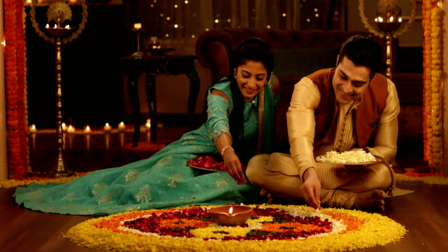 stockvideo's en b-roll-footage met ms happy husband and wife wearing traditional clothing making rangoli with flowers during diwali festival / delhi, india - in kleermakerszit