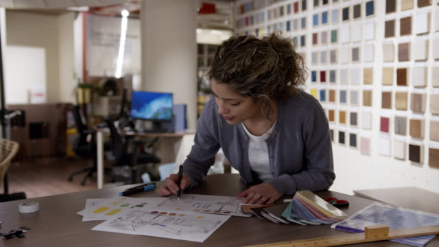 happy interior designer drawing sketches while at a furniture store - interior designer stock videos & royalty-free footage