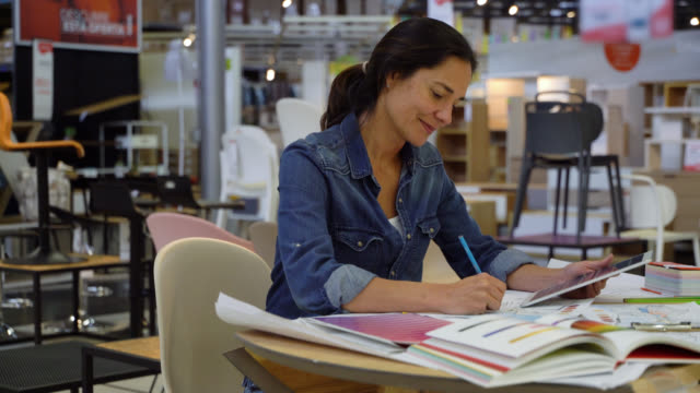 happy interior designer working on a sketch and holding a tablet at a furniture store - architect stock videos & royalty-free footage