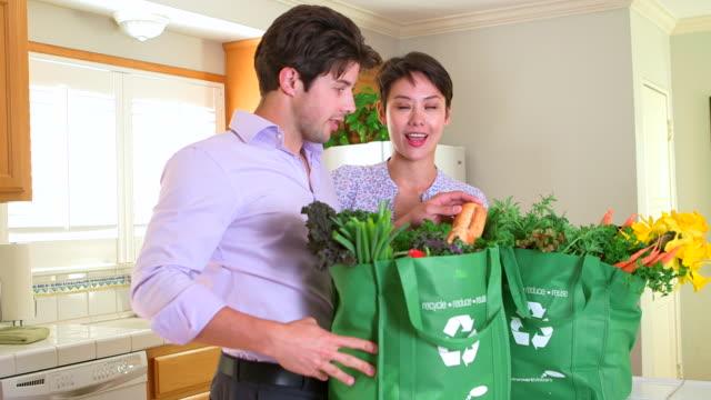vidéos et rushes de happy interracial couple coming home with groceries - plein