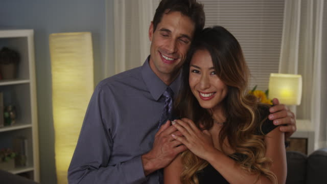 happy interracial couple smiling at camera - menschliche gliedmaßen stock-videos und b-roll-filmmaterial