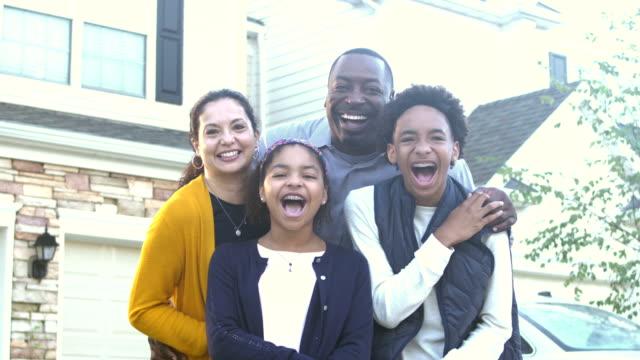 glückliche interrassische familie vor dem haus, verspielt - 14 15 years stock-videos und b-roll-filmmaterial