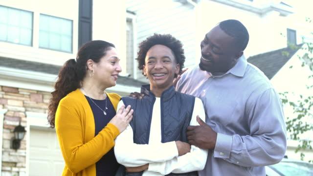 happy interracial family in front of home - davanti video stock e b–roll