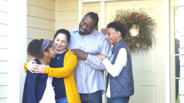 vídeos de stock e filmes b-roll de happy interracial family in front of home - 14 15 years