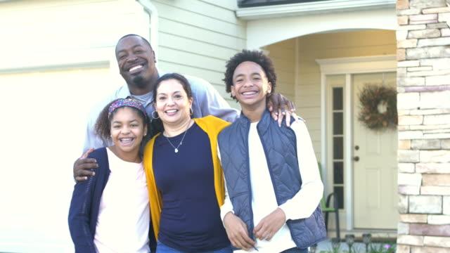家の前で幸せな異人種間の家族 - 建物入口点の映像素材/bロール