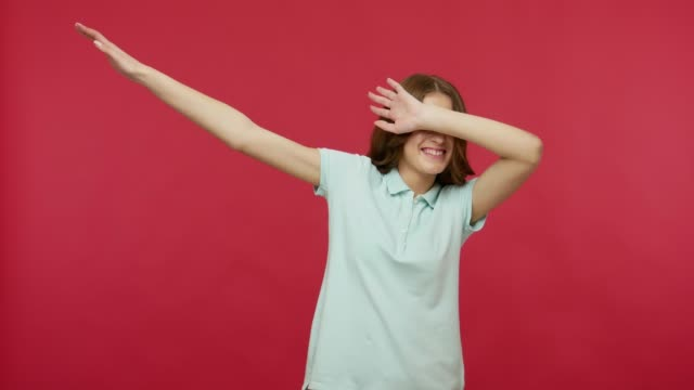 Happy joyful young woman in polo t-shirt celebrating success with dab dance move, famous internet meme