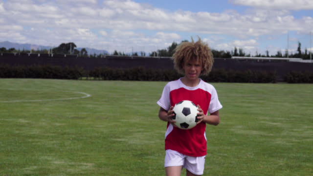 vídeos de stock e filmes b-roll de happy kid at a soccer field holding a ball while facing camera smiling - equipamento de equipa