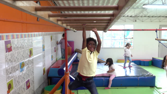 happy kids playing at the indoor park at school having fun - parco giochi video stock e b–roll