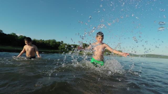 happy kids splashing water at the lake,contrasting sparkling sunset light. - badeshorts stock-videos und b-roll-filmmaterial