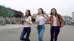 Happy korean friends running together