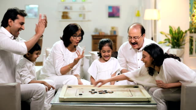 happy large family playing carrom in the home, delhi, india - från indiska subkontinenten bildbanksvideor och videomaterial från bakom kulisserna