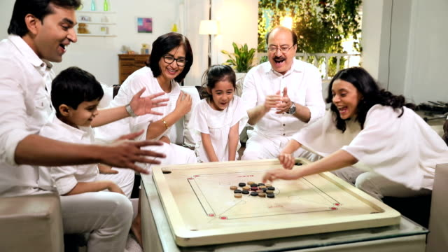 happy large family playing carrom in the home, delhi, india - carrom stock videos & royalty-free footage