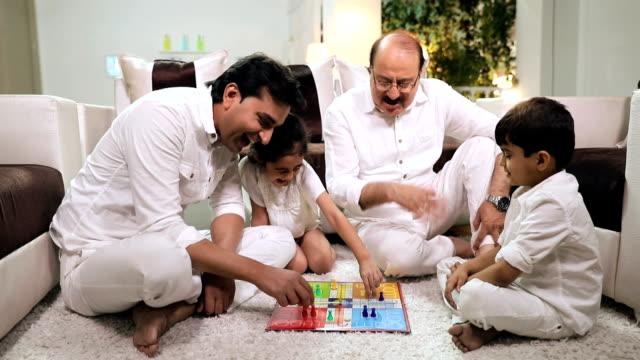 happy large family playing ludo in the home, delhi, india - 余暇 ゲームナイト点の映像素材/bロール