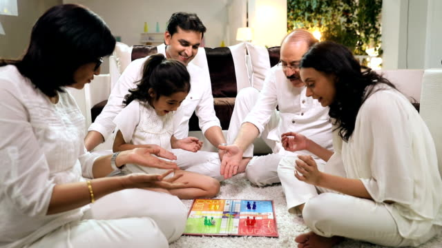 Happy large family playing ludo in the home, Delhi, India