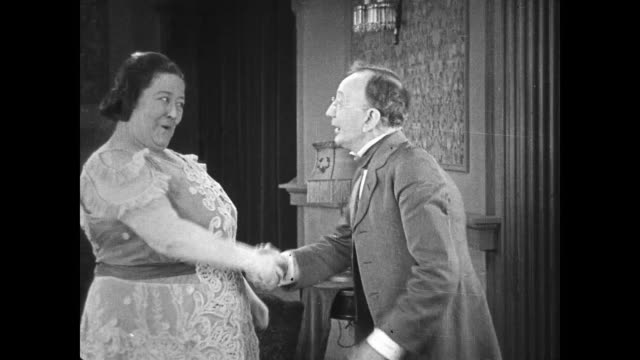 vidéos et rushes de 1922 happy larger woman shakes hands enthusiastically with wiry bespectacled older man - poignée objet manufacturé
