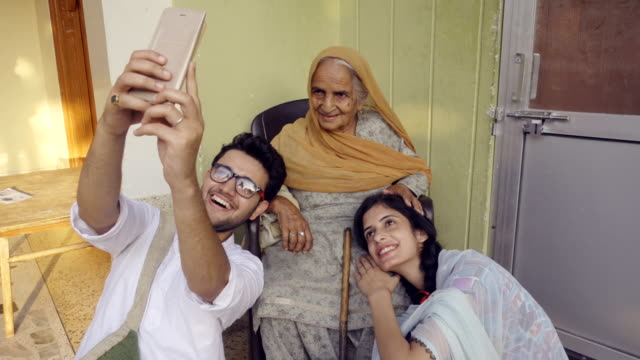 happy late teens taking selfie with grandmother. - indian ethnicity stock videos and b-roll footage