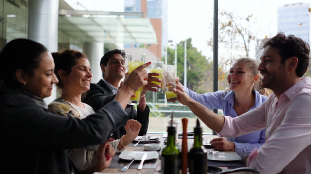 vídeos de stock, filmes e b-roll de executivos latin americanos felizes que apreciam bebidas durante uma reunião do almoço todos que sorriem e que fazem um brinde - roupa formal