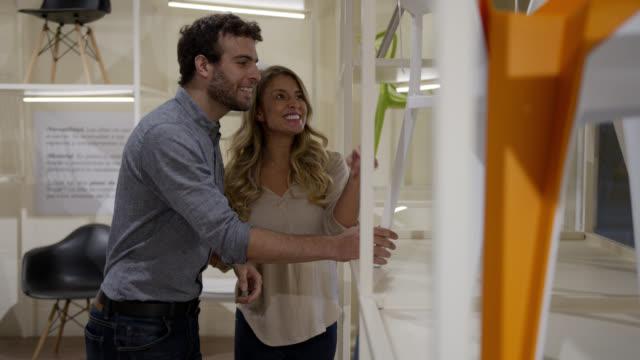 glückliches lateinamerikanisches paar kauft einen stuhl in einem möbelhaus - designer einrichtung stock-videos und b-roll-filmmaterial
