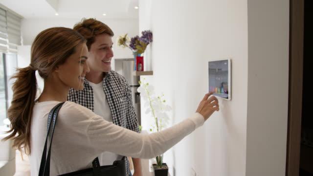 vídeos y material grabado en eventos de stock de feliz pareja latinoamericana encerrando su hogar inteligente a través de la tableta mientras habla - equipo de seguridad