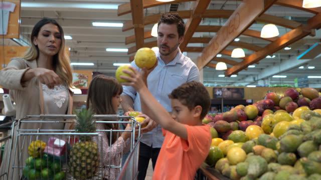 stockvideo's en b-roll-footage met happy latin american familie in de supermarkt winkelen voor boodschappen en kinderen kiezen fruit toe te voegen aan de winkelwagen - fruit