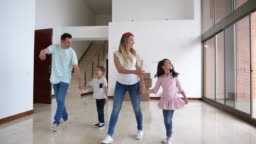 Happy latin american family with two kids walking into their new home and children excited looking at everything