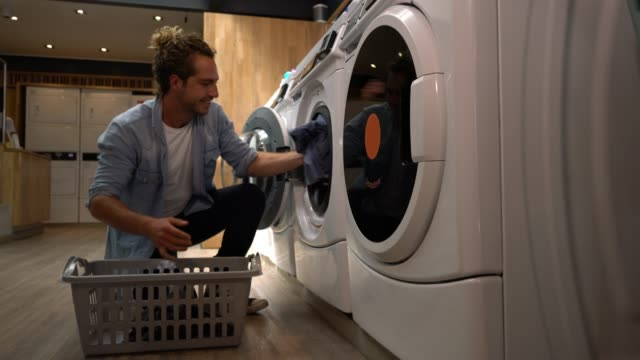 happy latin american male customer at a laundromat loading the washing machine - launderette stock videos and b-roll footage