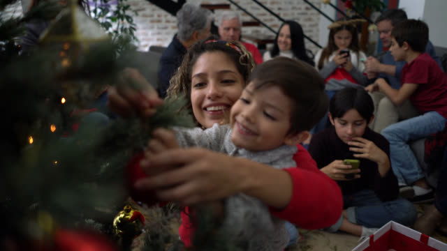 stockvideo's en b-roll-footage met gelukkig latijns-amerikaanse moeder en zoon opknoping ornamenten op een kerstboom glimlachend - latin american and hispanic ethnicity