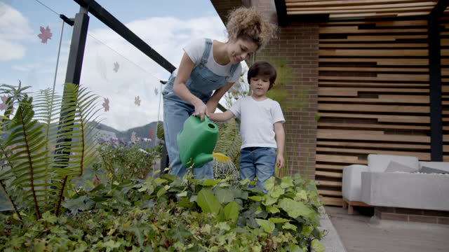 happy latin american mother teaching her son how to water the plants at their home garden - plant stock videos & royalty-free footage