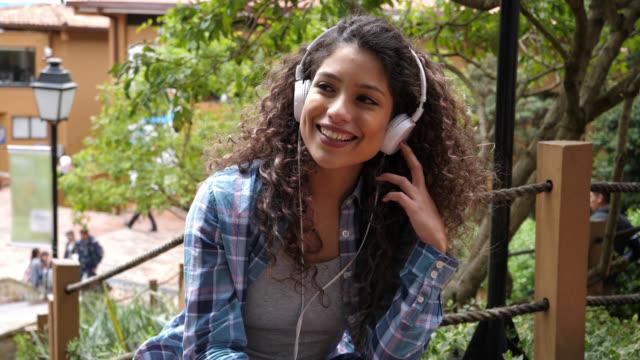 vídeos de stock, filmes e b-roll de feliz estudante latino-americano relaxante ao redor o colégio campus ouvir música com fones de ouvido - estudante universitária
