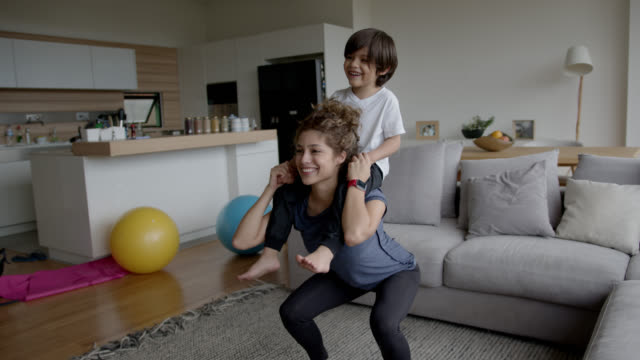 happy latin american woman exercising at home using her son as extra weight while she does squats - squatting position stock videos & royalty-free footage