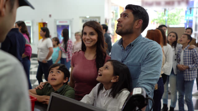 happy latin american young couple with their kids choosing snacks at the concession stand at the cinema - concession stand stock videos and b-roll footage
