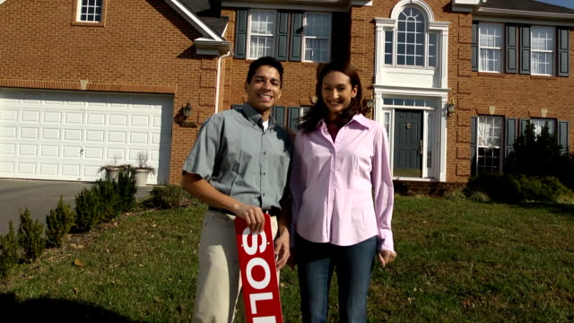 Happy Latin Couple Holding SOLD Sign