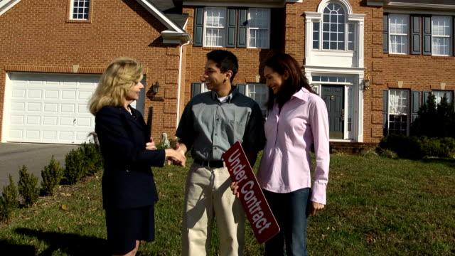 coppia felice con agente latina tenendo sotto contratto di - cartello di agenzia immobiliare video stock e b–roll