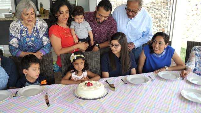 vídeos de stock e filmes b-roll de happy latin family celebrating young girls's birthday at home. - família com quatro filhos